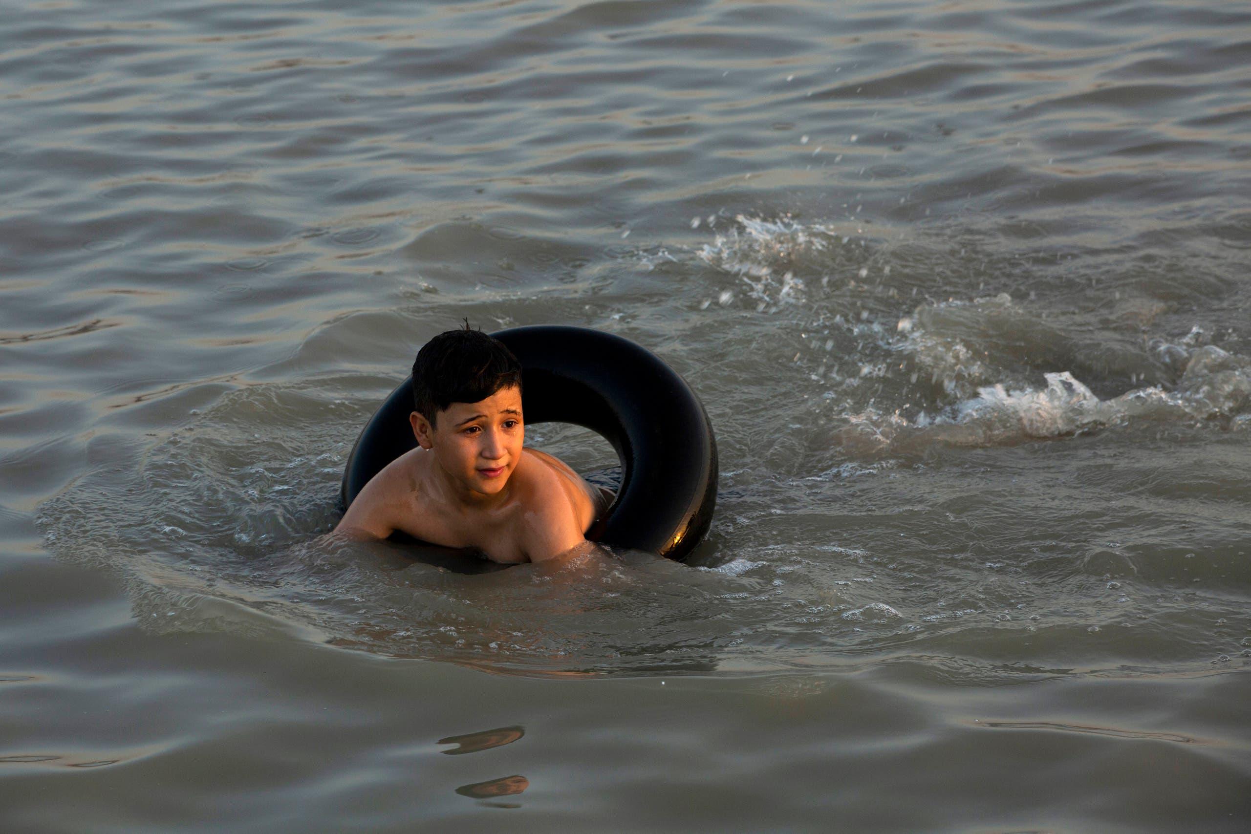 عراقيون يلجأون إلى الأنهر والمياه هربا من حر الصيف وسط انقطاع الكهرباء (فرانس برس)