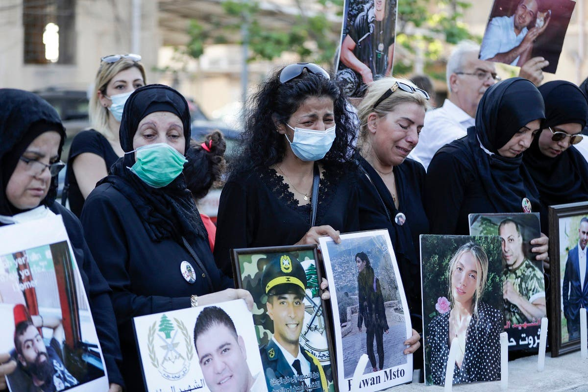 Relatives of victims of Beirut's port blast hold their pictures as they rally in the Lebanese capital on July 4, 2021. (Anwar Amro/AFP)