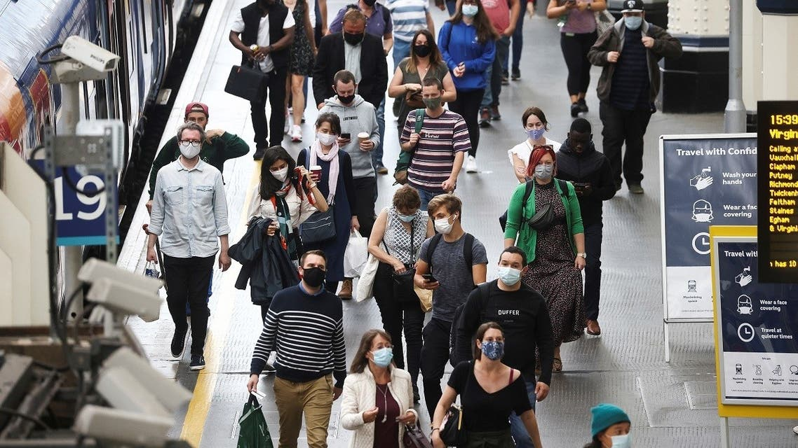 People, some wearing protective face masks, walk through Waterloo Station, amid the coronavirus disease, in London, Britain, July 4, 2021. (Reuters/Henry Nicholls)