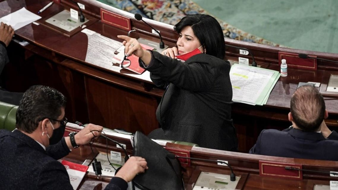 Abir Moussi (C), president of the Free Destourian Party (PLD), lifts her face mask as she gestures during a parliamentary session as Tunisian lawmakers debate ahead of a confidence vote on the new government reshuffle by the prime minister at the Tunisian Assembly headquarters in the capital Tunis on January 26, 2021. (AFP)