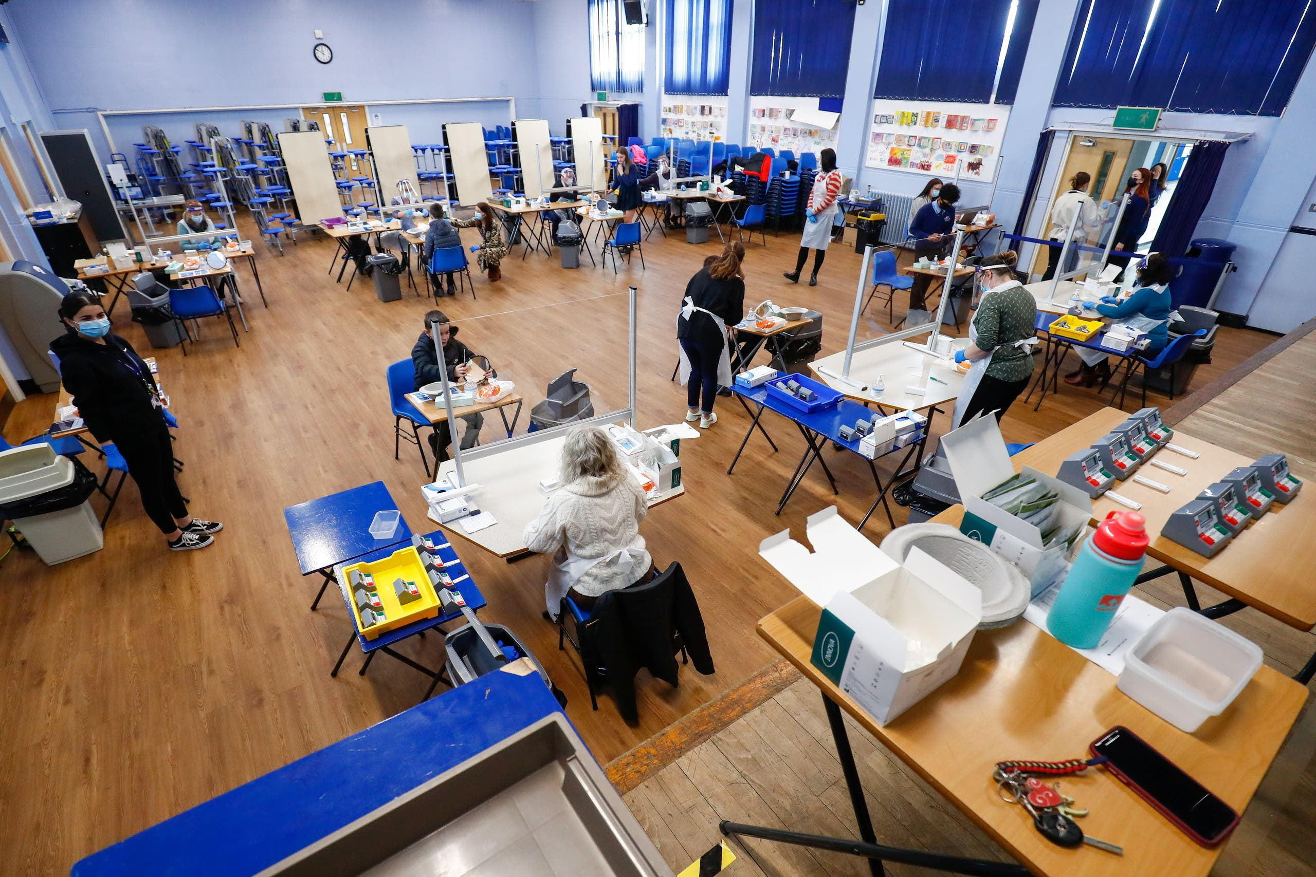 Students take lateral flow tests as health workers supervise at Weaverham High School, as the coronavirus disease (COVID-19) lockdown begins to ease, in Cheshire, Britain, March 9, 2021. (Reuters)