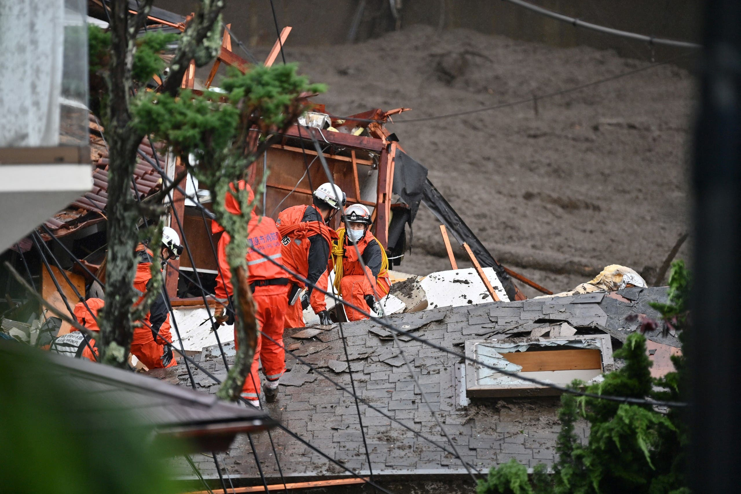 Firefighters search for missing people at the scene of a landslide following days of heavy rain in Atami in Shizuoka Prefecture on July 4, 2021. A huge landslide swept away homes and left 19 people missing at a popular resort town in central Japan on July 3 after days of heavy rain, local officials said.