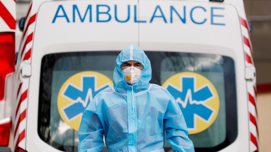 A medical worker wearing protective gear stands next to an ambulance outside a hospital for patients infected with COVID-19 in Kiev, Ukraine, November 24, 2020. (Reuters/Gleb Garanich)