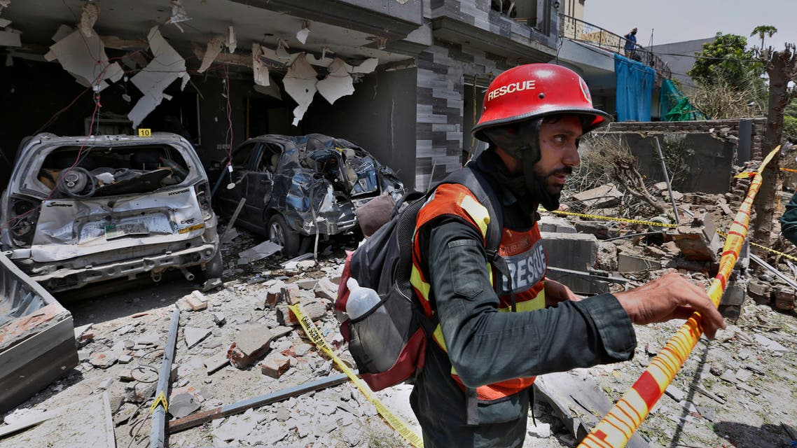 In this June 23, 2021 file photo, a rescue worker examines the site of explosion in Lahore, Pakistan. In a news conference Sunday, July 4, 2021, in Islamabad, Moeed Yousuf, Pakistan's national security advisor, accused India of orchestrating teh June 23 deadly car bombing in the eastern city of Lahore, saying that an investigation has shown it was organized by an unnamed Indian intelligence operative. (AP)