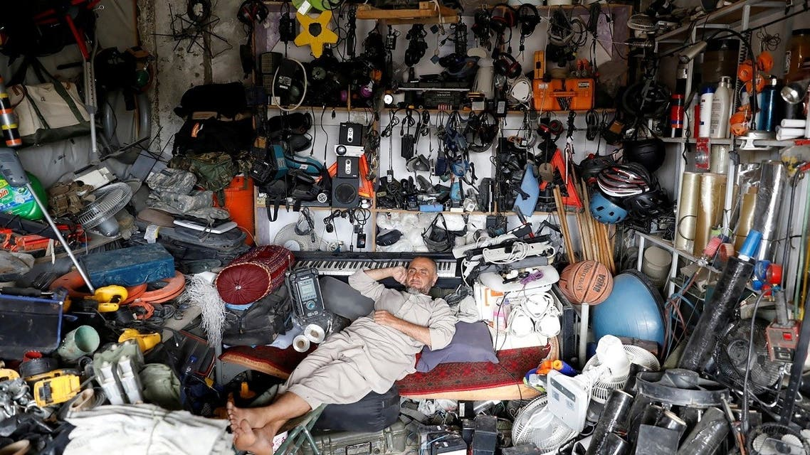 An Afghan man rests in his shop as he sells US second-hand materials outside Bagram US air base, Afghanistan July 5, 2021. (Reuters)