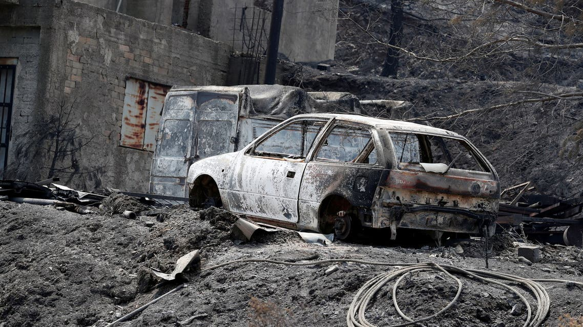 Burned house and cars are seen following a wildfire near the village of Melini, in the Larnaca mountain region, Cyprus July 4, 2021. (Reuters)