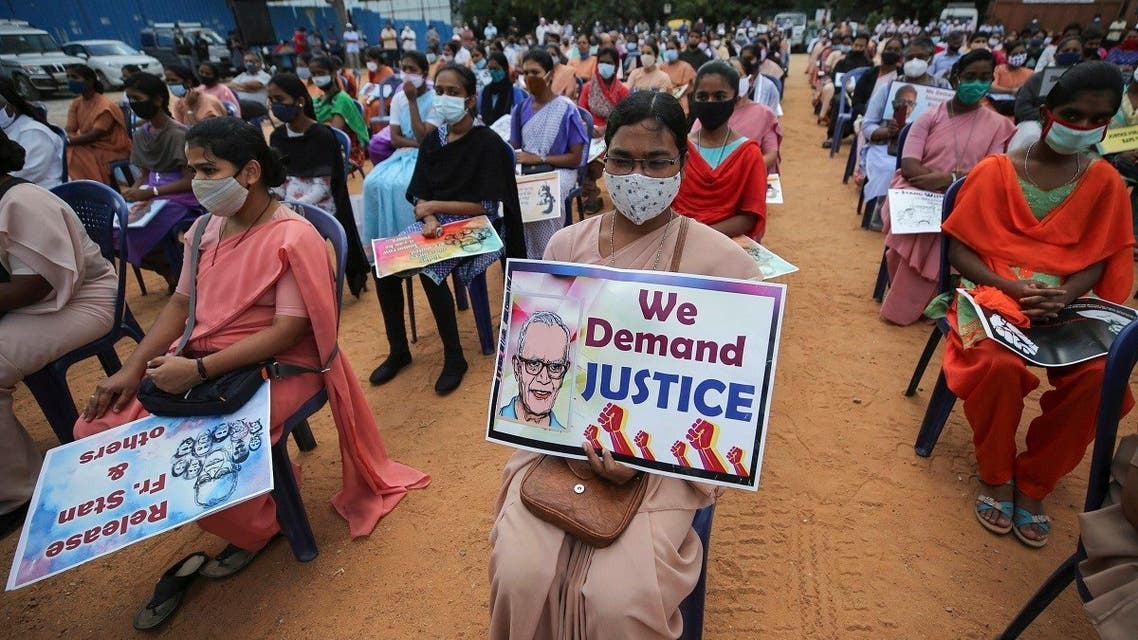A Christian nun, center, and others hold placards demanding the release of tribal rights activist Stan Swamy as they listen to a speaker during a demonstration in Bengaluru, India, Nov.12, 2020. (AP/Aijaz Rahi)