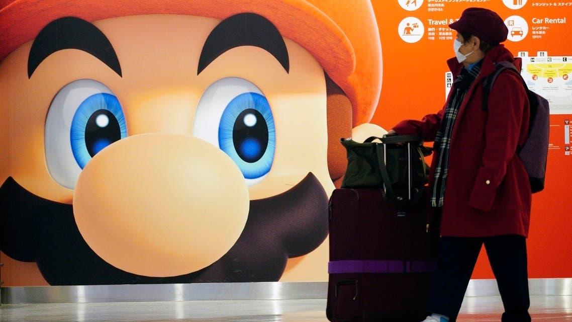 A traveler walks past a propaganda featuring Nintendo character at Narita airport in Narita, near Tokyo. (AP)