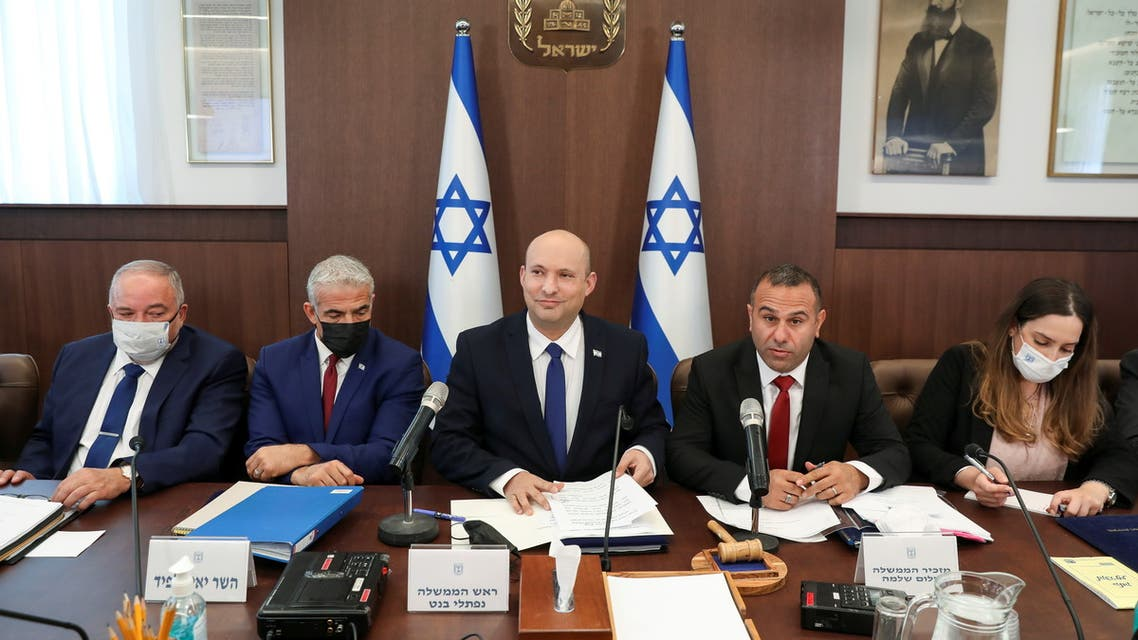 Israeli Prime Minister Naftali Bennett, sitting between Foreign Minister Yair Lapid and Government Secretary Shalom Shlomo, attends a weekly cabinet meeting at the prime minister's office in Jerusalem July 4, 2021. (Reuters)