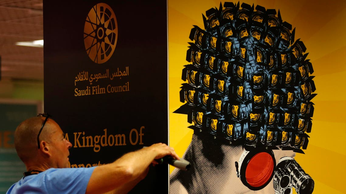 A worker installs a poster of the Saudi Film Council inside the Film Market business area in 2018. (File photo: Reuters)