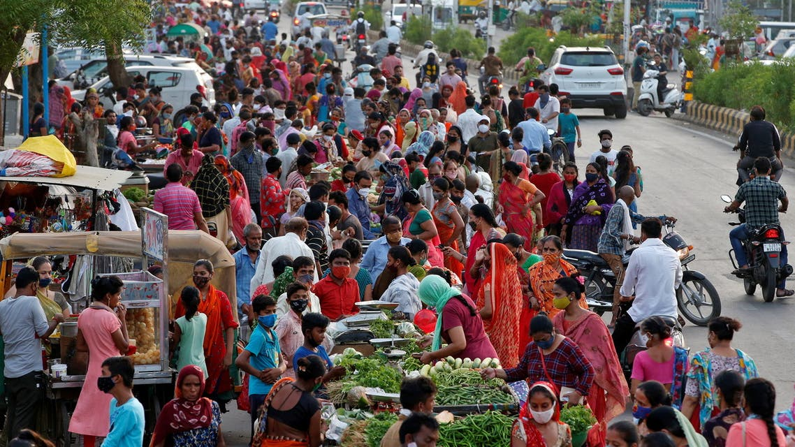 People shop at a crowded roadside vegetable market after authorities eased coronavirus restrictions, following a drop in COVID-19 cases in Ahmedabad, India, June 15, 2021. (Reuters)