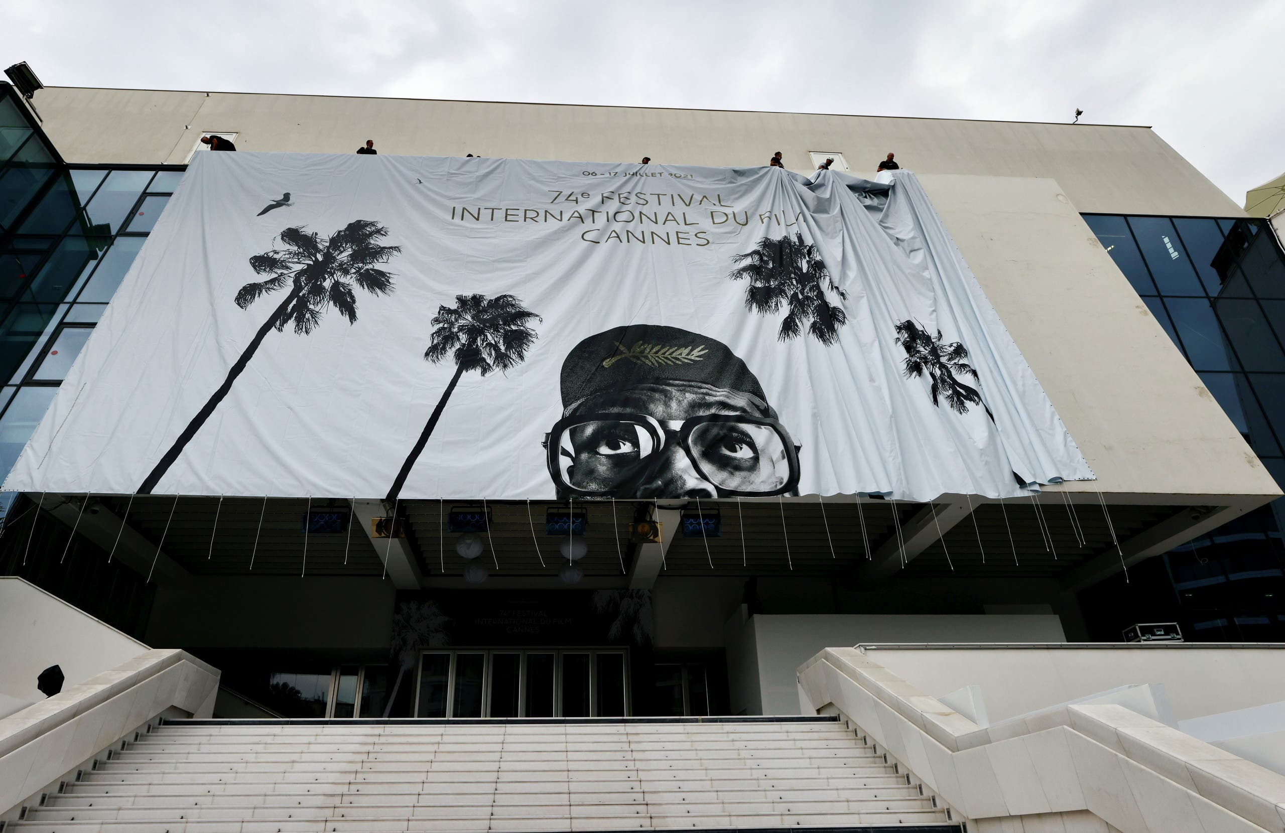 Workers set up a giant canvas of the official poster featuring Spike Lee on the facade of the festival palace, ahead of the opening ceremony of the 74th Cannes Film Festival, in Cannes, France, July 4, 2021. (Reuters)