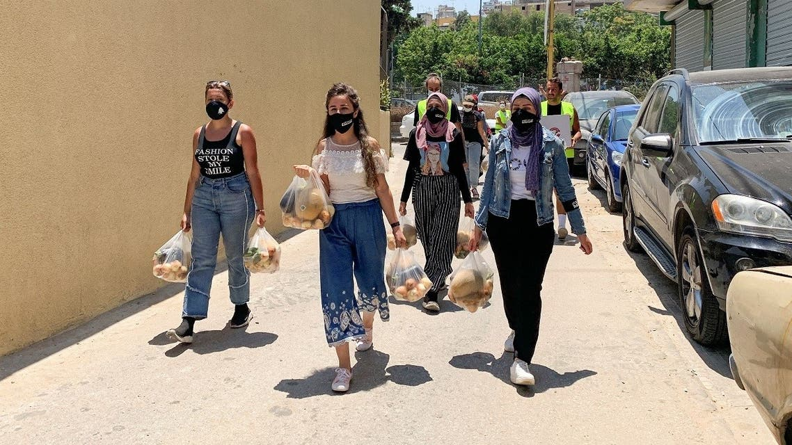 Volunteers from Base Camp, walk as they carry bags of vegetables to be distributed to people in need in Beirut, Lebanon July 1, 2021. (Reuters)