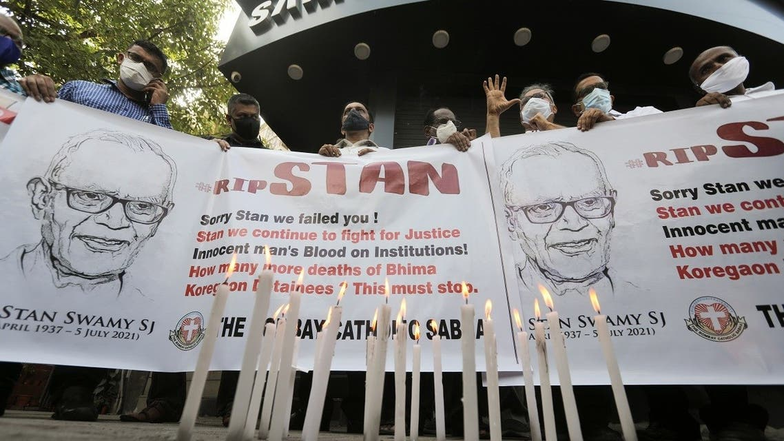 People hold a banner during a prayer meet for 84-year-old Indian Christian priest and activist Father Stanislaus Lourduswamy, commonly known as Stan Swamy, after he died in a hospital on Monday while awaiting bail after he was arrested under an anti-terrorism law, in Mumbai, India, on July 6, 2021. (Reuters)