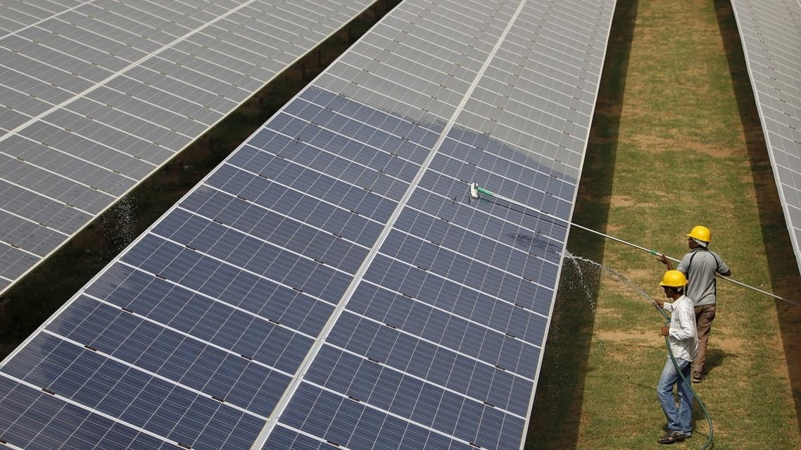 Workers clean photovoltaic panels inside a solar power plant in Gujarat, India. (Reuters)