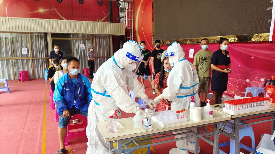 People line up for nucleic acid testing at a residential compound following new cases of the coronavirus disease (COVID-19) in Ruili, a border city with Myanmar, in Yunnan province, China July 5, 2021. (Reuters)