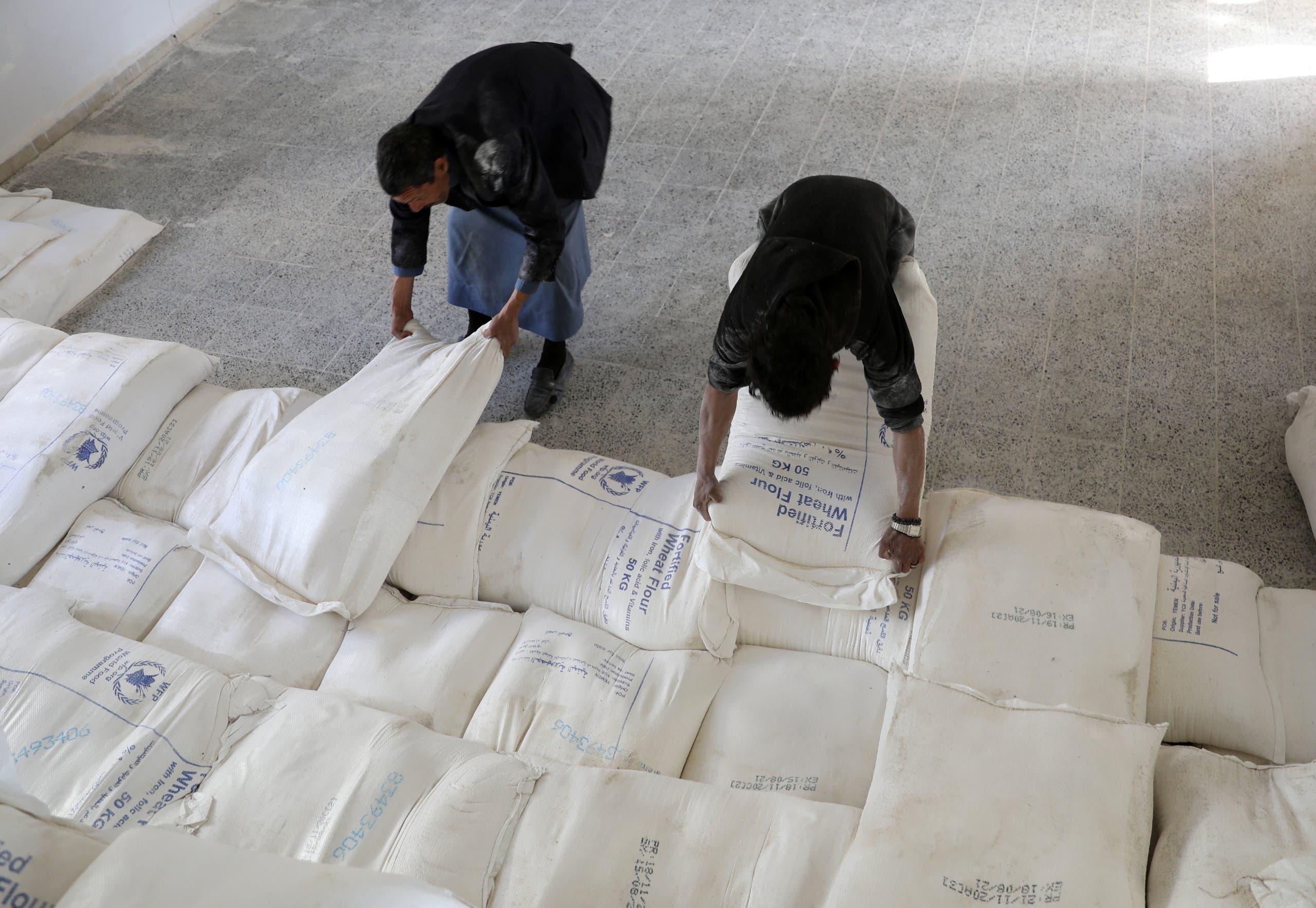امدادی سامان کے مرکز میں مزدور سیمنٹ کی بوریاں اٹھا رہے ہیں
