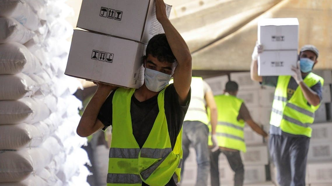 2021-07-07TWorkers carry boxes of humanitarian aid near Bab al-Hawa crossing at the Syrian-Turkish border, in Idlib governorate, Syria, on June 30, 2021. (Reuters)130126Z_733236774_RC2YAO9A69X5_RTRMADP_3_SYRIA-SECURITY-CROSSING