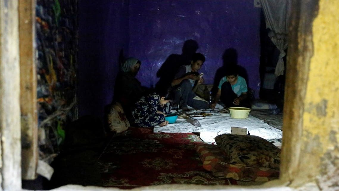 Iraqi children eat dinner at home during a power cut in Baghdad, Iraq July 3, 2021. (Reuters)