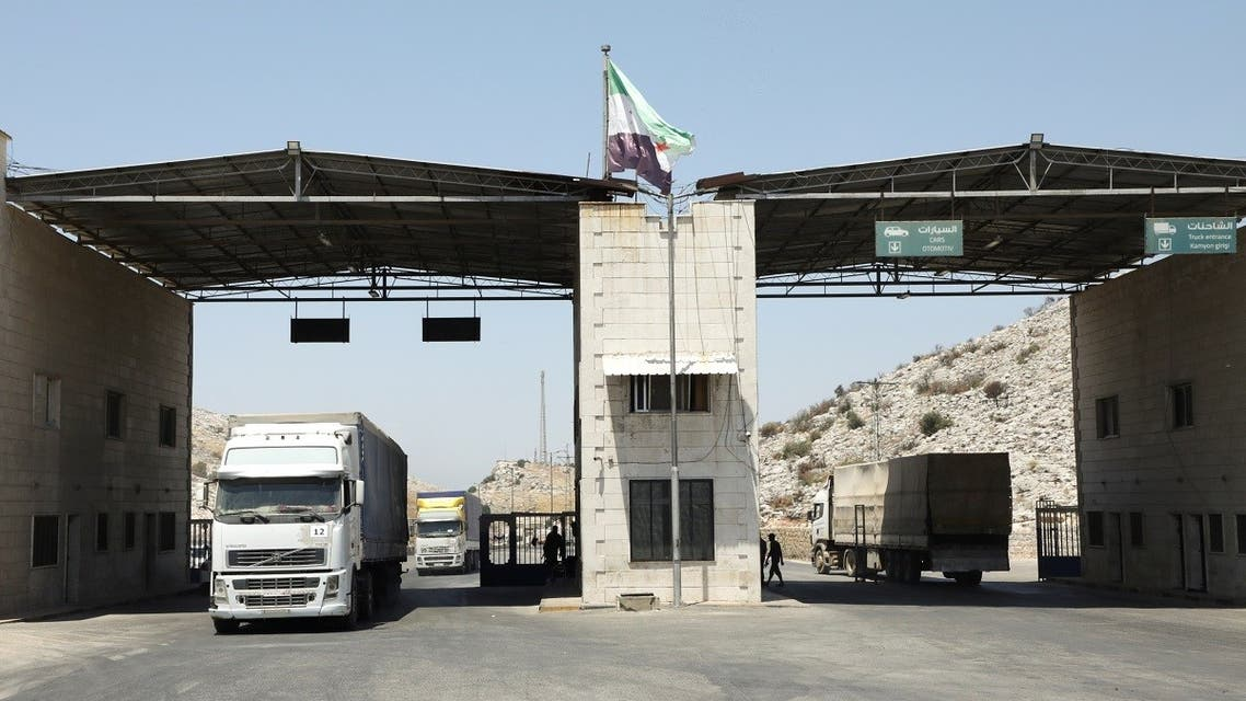 Trucks drive at Bab al-Hawa crossing at the Syrian-Turkish border, in Idlib governorate, Syria, on June 30, 2021. (Reuters)