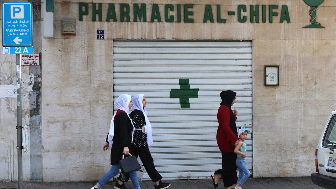 People walk in front of the shuttred door of a pharmacy in the Lebanese capital Beirut, during a nationwide strike of pharmacies to protest against a severe shortage of medicine, on July 9, 2021. (File photo: AFP)