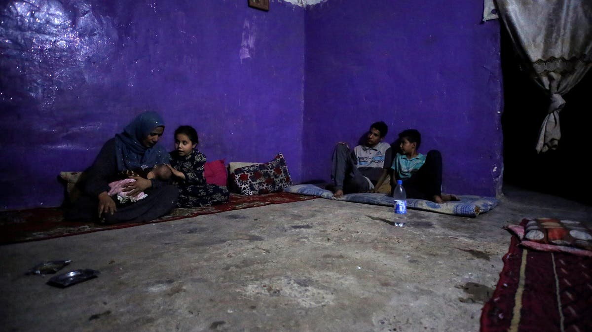 An Iraqi family sits in their house during a power cut in Baghdad, Iraq, on July 3, 2021. (Reuters)