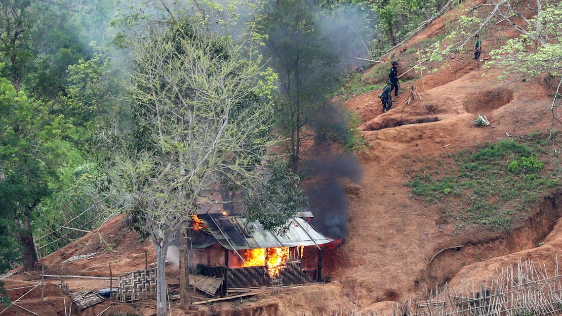 Ethnic minority Karen troops are seen after setting fire to a building inside a Myanmar army outpost near the Thai border, which is seen from the Thai side on the Thanlwin, also known as Salween, riverbank in Mae Hong Son province, Thailand, April 28, 2021. (Reuters)