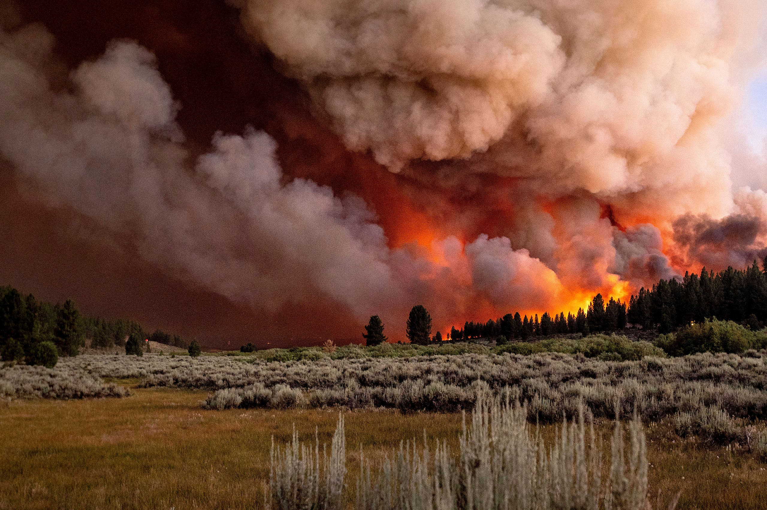 Plumes of smoke and fire rise above Frenchman Lake as the Sugar Fire, part of the Beckwourth Complex Fire, burns in Plumas National Forest, California, on Thursday, July 8, 2021. (AP)