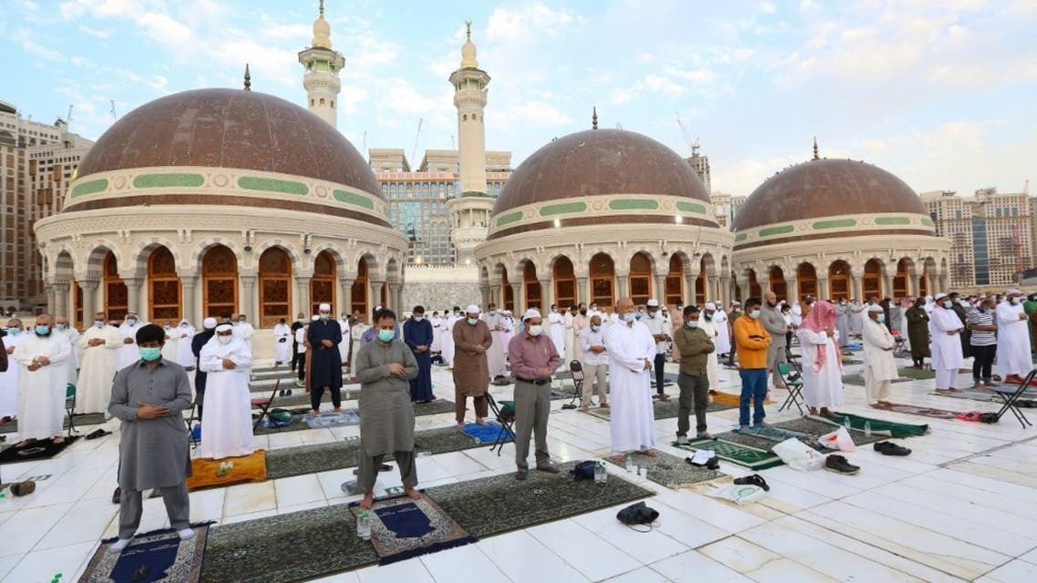 Muslim worshippers perform the Eid al-Fitr morning prayer at the Grand Mosque in Saudi Arabia's holy city of Mecca to mark the end of the fasting month of Ramadan, on May 13, 2021. (AFP)