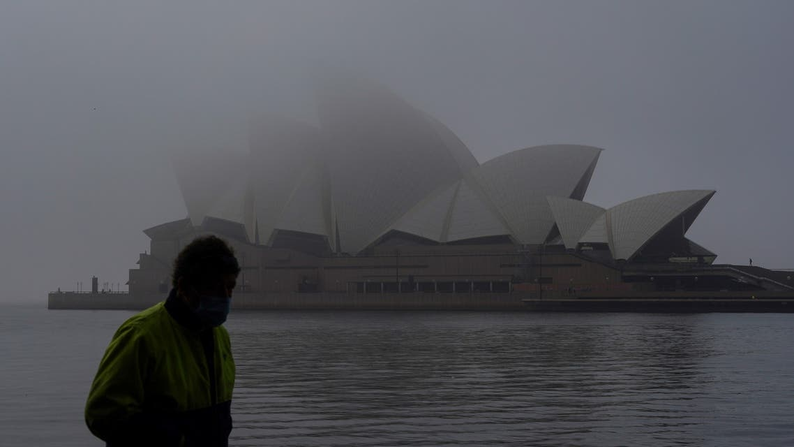 A man wearing a protective face mask walks past the Sydney Opera House, seen shrouded in fog, during a lockdown to curb the spread of a coronavirus disease (COVID-19) outbreak in Sydney, Australia, July 1, 2021. (Reuters)