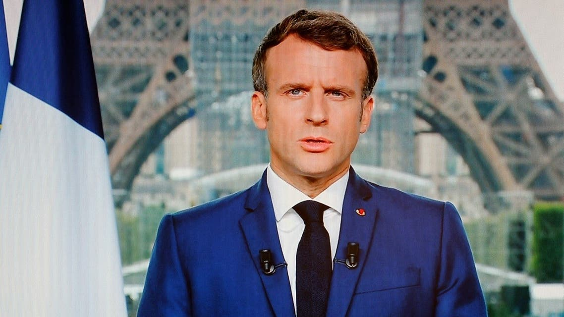 French President Emmanuel Macron is seen on a TV screen as he speaks during a televised address to the nation from the temporary Grand Palais in Paris on July 12, 2021. (Ludovic Marin/AFP)