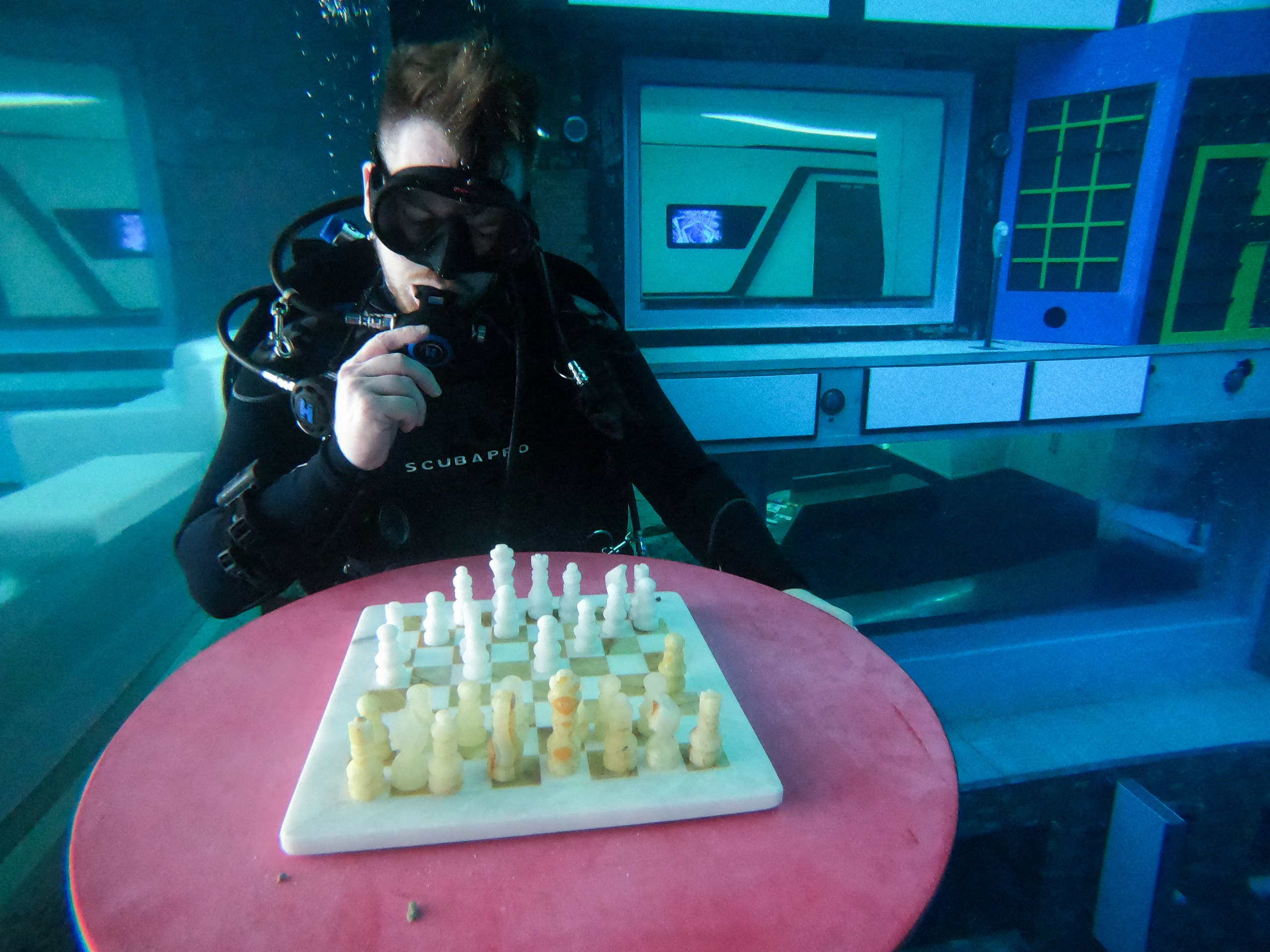 A diver plays mock chess as he experiences Deep Dive Dubai, the deepest swimming pool in the world reaching 60m, in the United Arab Emirates, on July 10, 2021. (AFP)