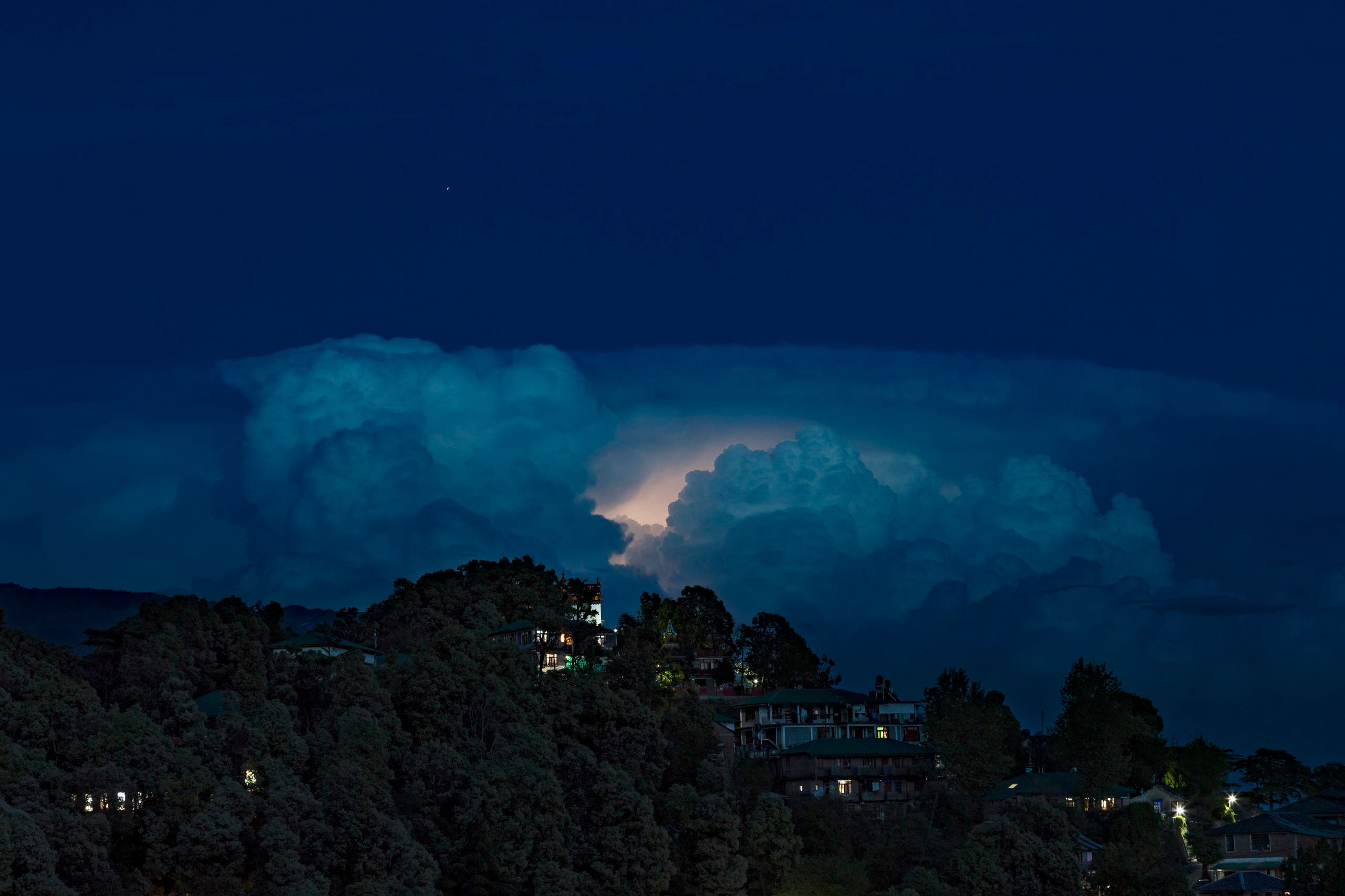 A flash of lightning lights up a raincloud hovering over a township in Dharmsala, India, Sunday, April 19, 2020. (File photo: AP)