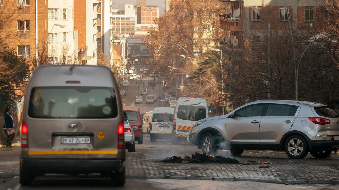 Cars drive around a burning tire on the street in Hillbrow, Johannesburg, South Africa, Sunday, July 11, 2021. (AP/Themba Hadebe)