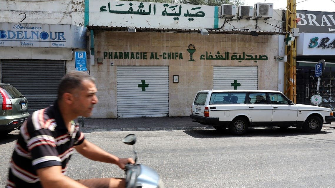 A man drives his scooter past the shuttered door of a pharmacy in the Lebanese capital Beirut, during a nationwide strike of pharmacies to protest against a severe shortage of medicine, on July 9, 2021. (AFP)