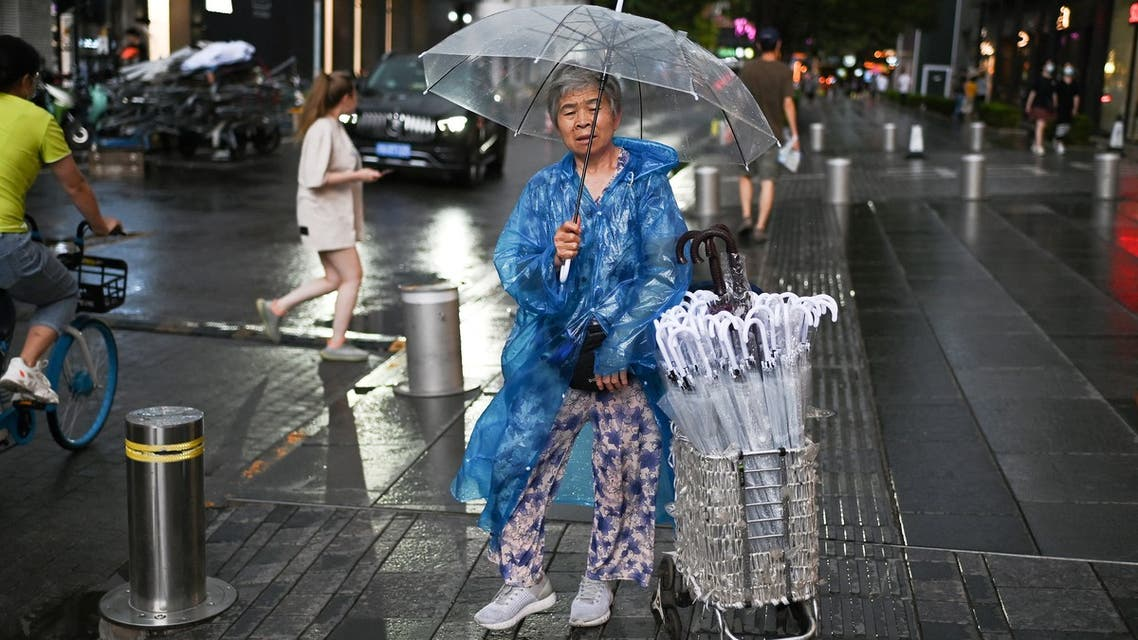 A woman sells umbrellas outside a shopping mall after a rain shower in Beijing on July 8, 2021. (File photo: AFP)