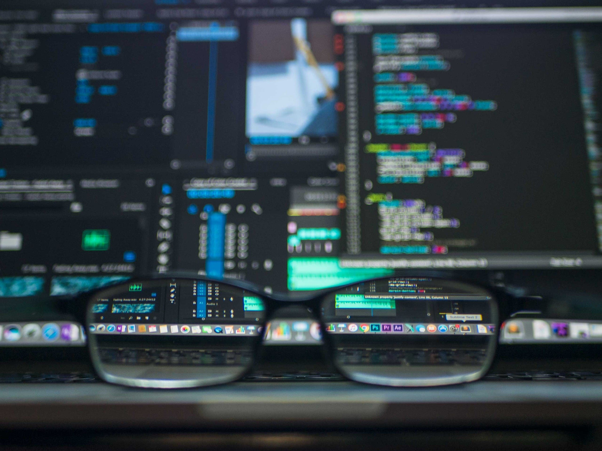 Glasses placed on a desk with a computer monitor in the background. (Unsplash, Kevin Ku)