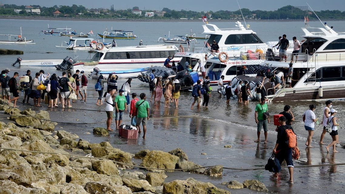 This picture taken on January 7, 2021 shows tourists preparing to board a fast boat from Sanur beach near Denpasar on Indonesia's resort island of Bali. (Sonny Tumbelaka/AFP)
