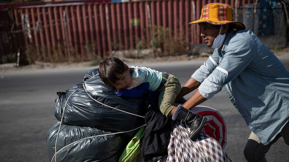 An Afghan migrant pushes a cart with his son and their belongings, following a fire at the Moria camp on the island of Lesbos, Greece, September 11, 2020. (Reuters)