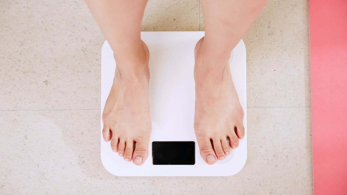Person standing on white digital scale to measure their body weight. (Unsplash, Yunmai)