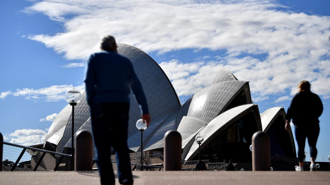 This picture taken on June 26, 2021 shows people walking in front of the Opera House, usually packed with visitors, as a lockdown in Australia's largest city Sydney was tightened on July 9, 2021 due to new Covid-19 infections hit a record and authorities warned an outbreak of the Delta variant was spinning out of control. (File photo: AFP)