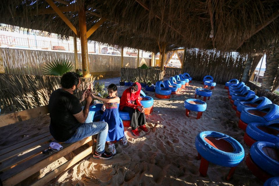 Palestinian beachgoers sit on chairs that have been made of car tires at an environment-friendly beachfront cafe in Gaza, on July 8, 2021. (Reuters)