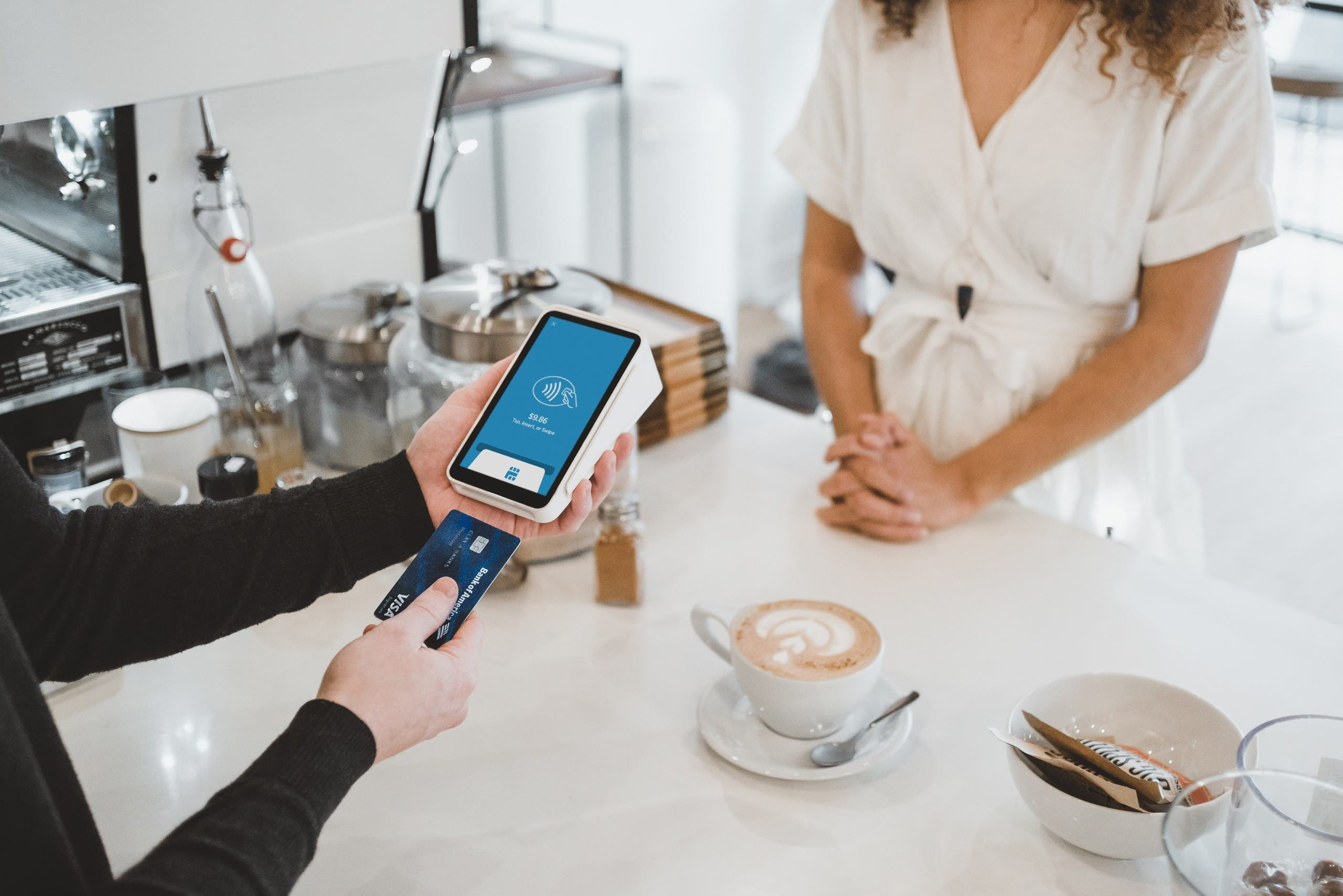 Woman makes a payment using her card at a coffee shop. (Unsplash, Clay Banks)