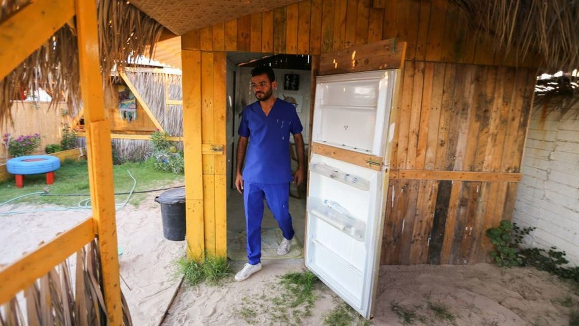 Palestinian artist, Ali Mhana, leaves his office through a fridge door at an environment-friendly beachfront cafe in Gaza, on July 8, 2021. (Reuters)