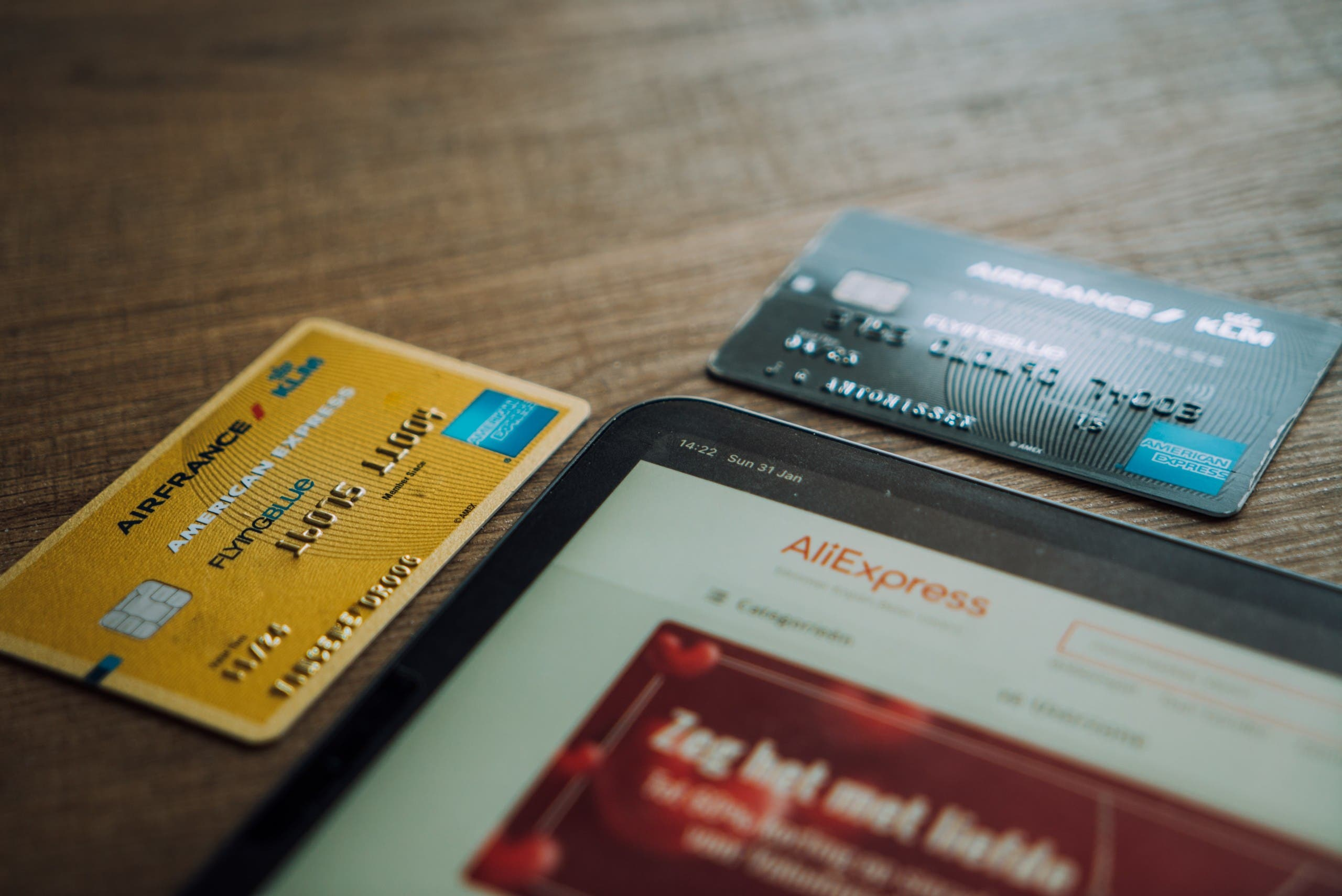 Two debit cards laid out next to an iPad displaying ecommerce website AliExpress. (Unsplash, Cardmapr.nl)