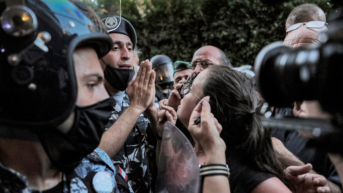 A protester argues with security forces as demonstrators and families of the Beirut blast victims gather outside the residence of Lebanon's Interior Minister, July 13, 2021. (AFP)