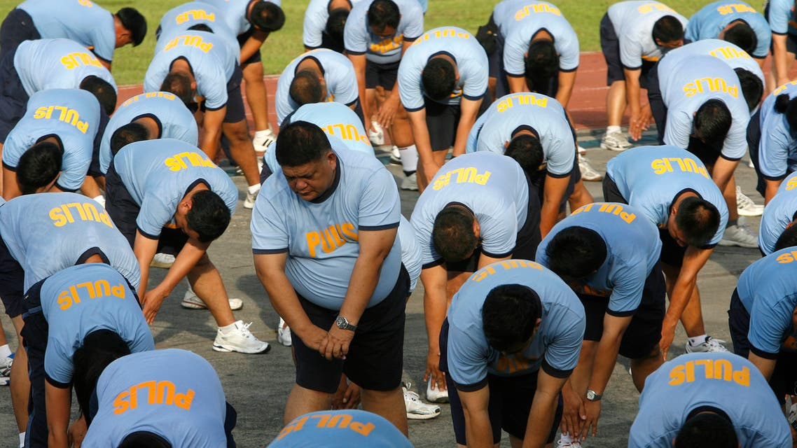 Police officers stretch before an exercise during their Weight Loss Management Program at Camp Crame in Quezon City Metro Manila June 19, 2012. (Reuters)