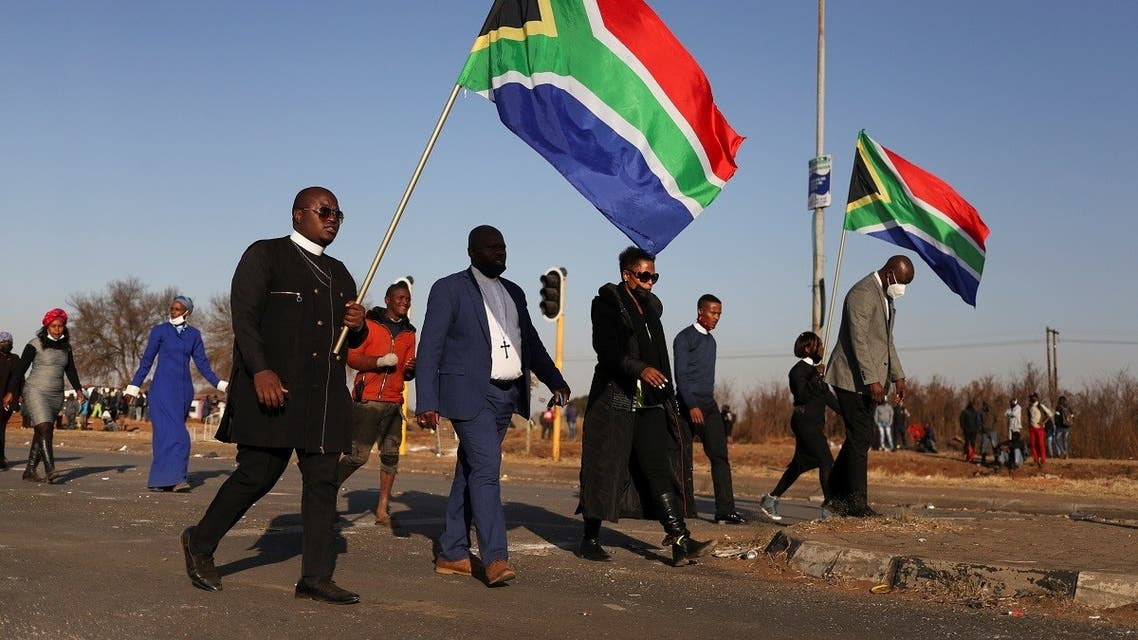 Protesters carrying South African flags walk near a looted shopping mall as the country deploys army to quell unrest linked to the jailing of former South African President Jacob Zuma, in Vosloorus, South Africa, July 14, 2021. (Reuters/Siphiwe Sibeko)