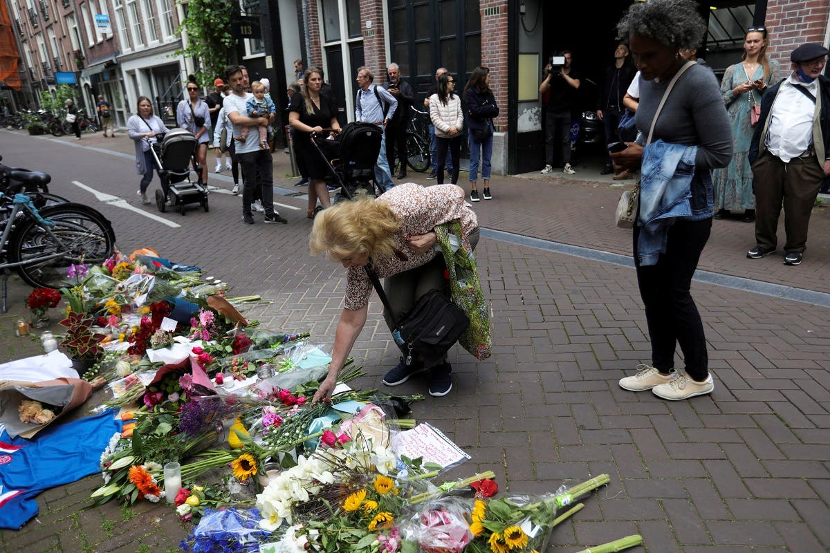 A woman leaves flowers where Dutch celebrity crime reporter Peter R. de Vries has been shot and reported seriously injured in Amsterdam, Netherlands, on July 7, 2021. (Reuters)