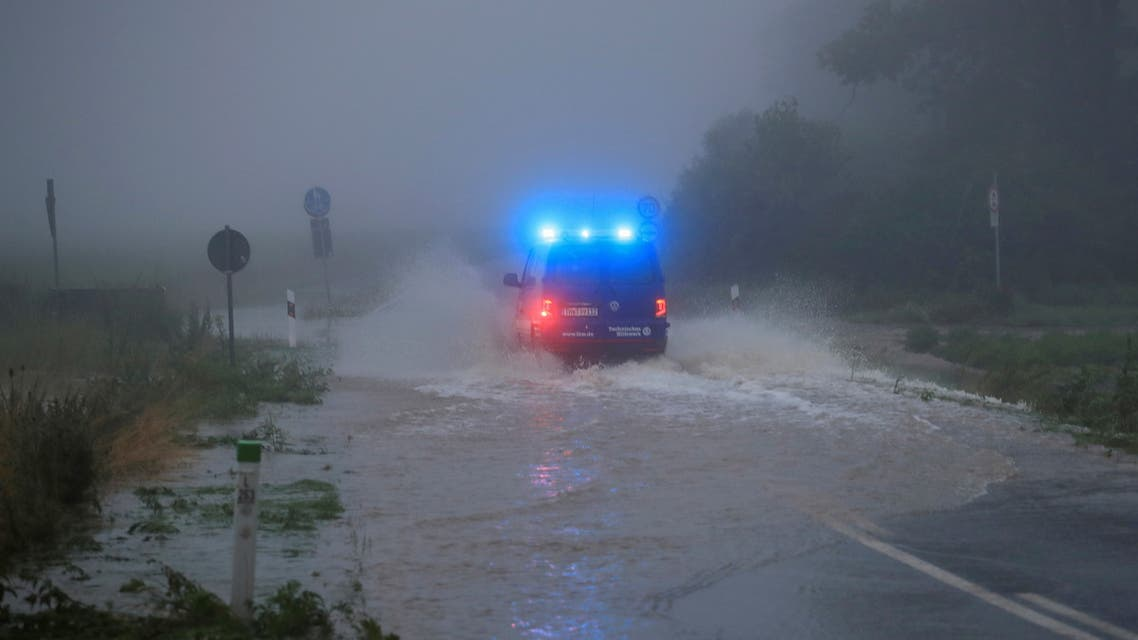 A vehicle travels on a flood affected road after the Erft river swelled following heavy rainfalls in Erftstadt, near Cologne, Germany, July 15, 2021. (Reuters)